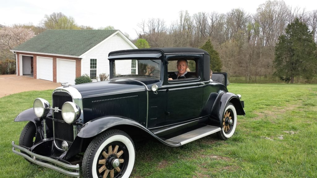 Guy taking the grand kids for a ride in his '31 Buick
